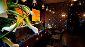 Night time view of the ella bar and foyer at noor in los angeles