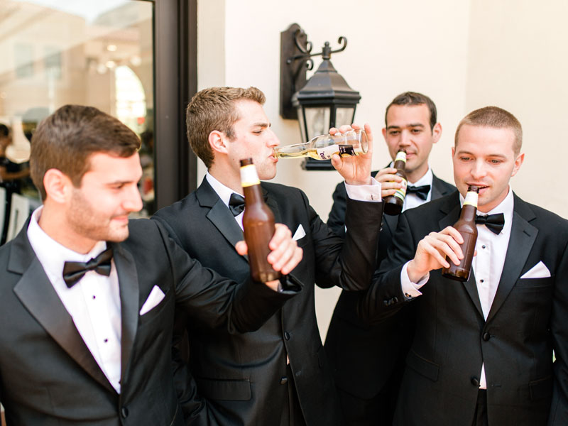 groom with groomsmen enjoying a beer