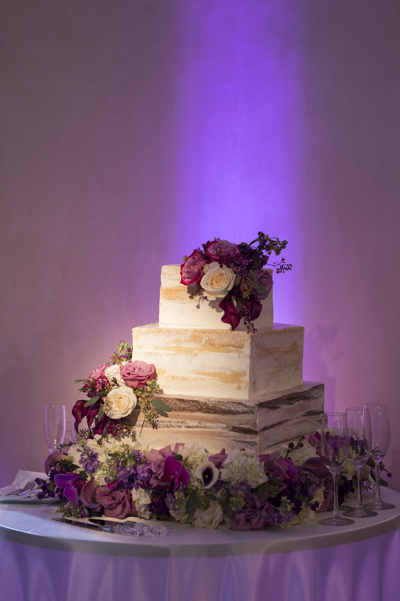 square nearly naked wedding cake covered in roses at noor los angeles banquet hall