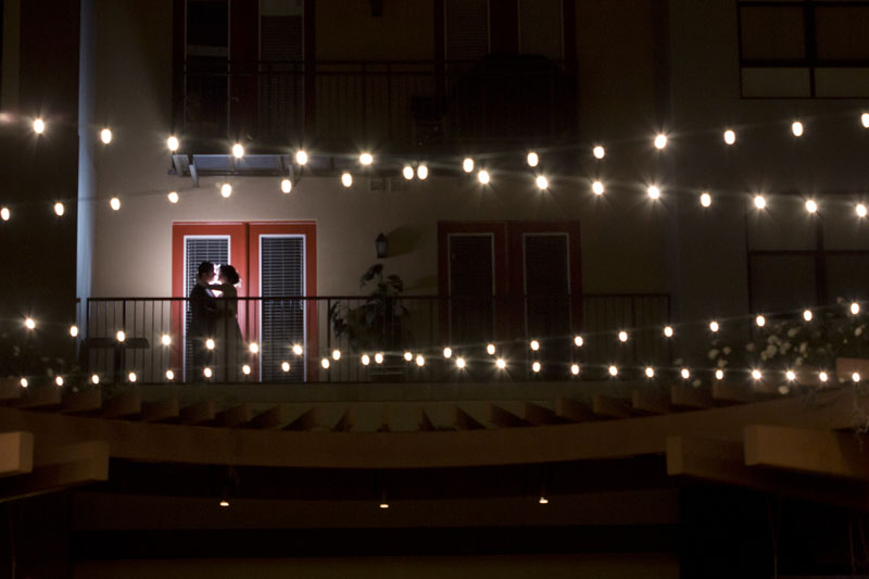bride and groom kissing in silhouette on the balcony of the NOOR wedding suite