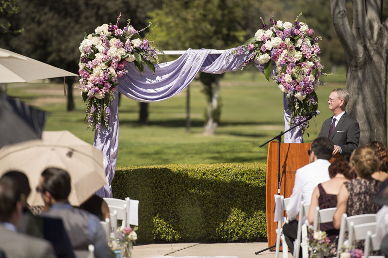 wedding arch draped with lilac fabric and roses