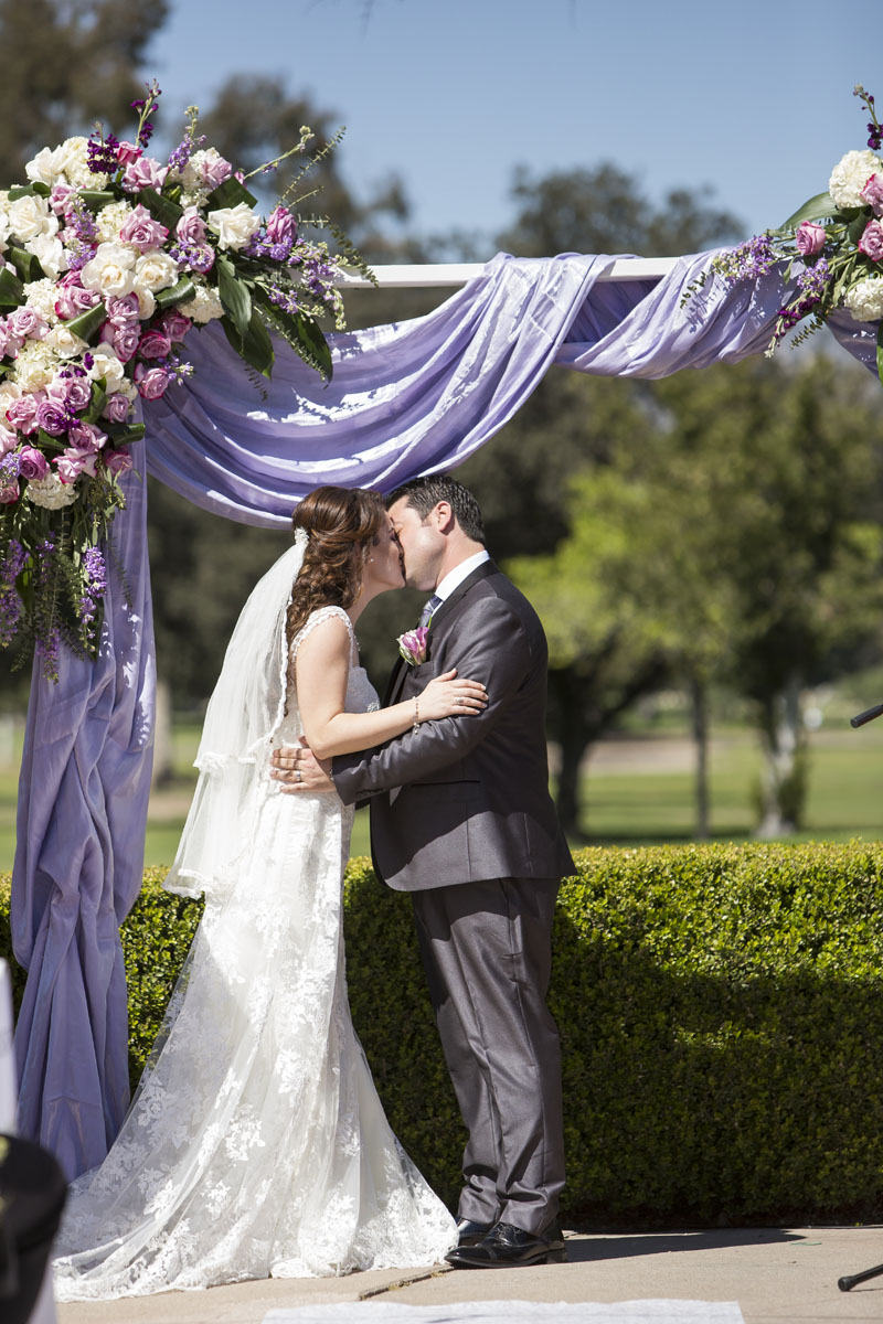 bride and groom first kiss underneath a beautiful wedding arch los angeles wedding