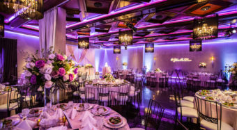 wedding reception view of the ella banquet hall with floral arrangements and chandeliers