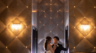 romantic portrait of bride and groom in the ella banquet hall foyer with soft lighting and large chandelier