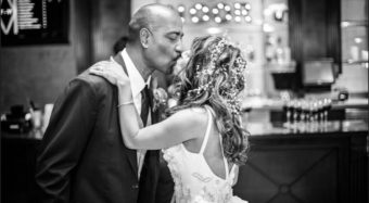 wedding portrait in black and white of the bride and groom kissing in the ella bar and foyer at noor los angeles