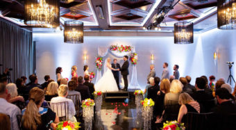 bride and groom exchanging vows under a floral arch in the ella ballroom banquet hall at noor los angeles