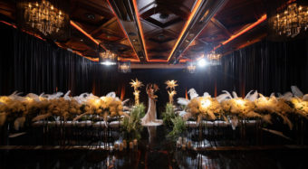 mardi gras themed wedding ceremony with floral arrangements and bride and groom
