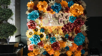 flower wall with orange blue and yellow paper flowers on the ella banquet hall patio