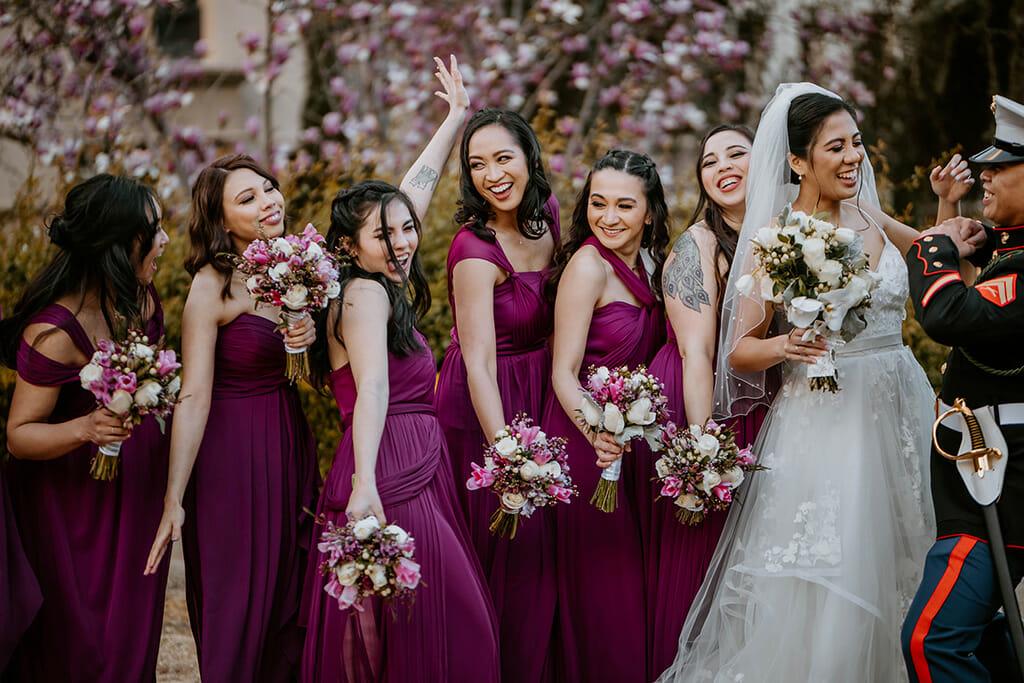 bridesmaids in burgundy laughing with bride and groom NOOR pasadena wedding