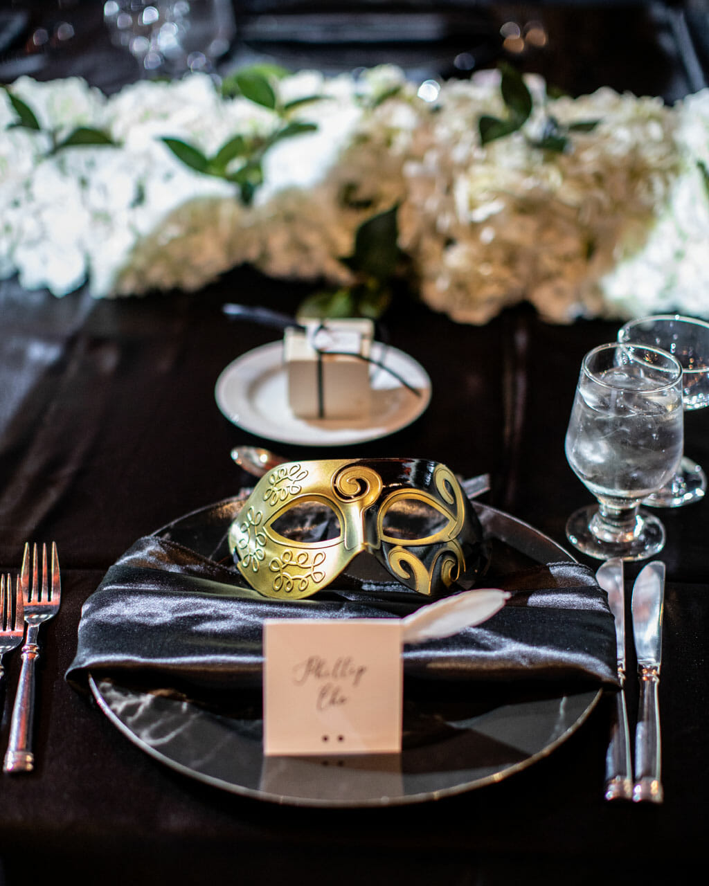 mardi gras themed wedding reception table setup with gold mask and black linen