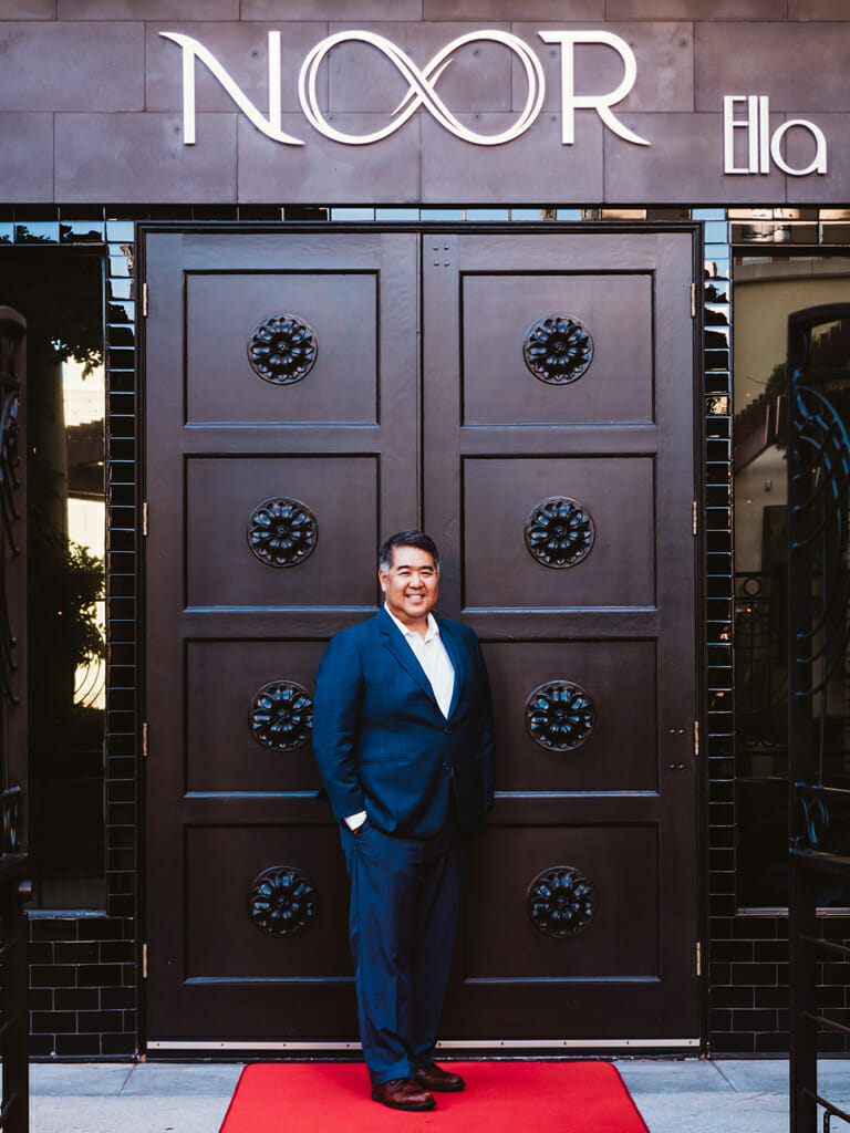 Kenji Shimabukuro events manager at noor los angeles standing outside ella banquet hall black carved double doors