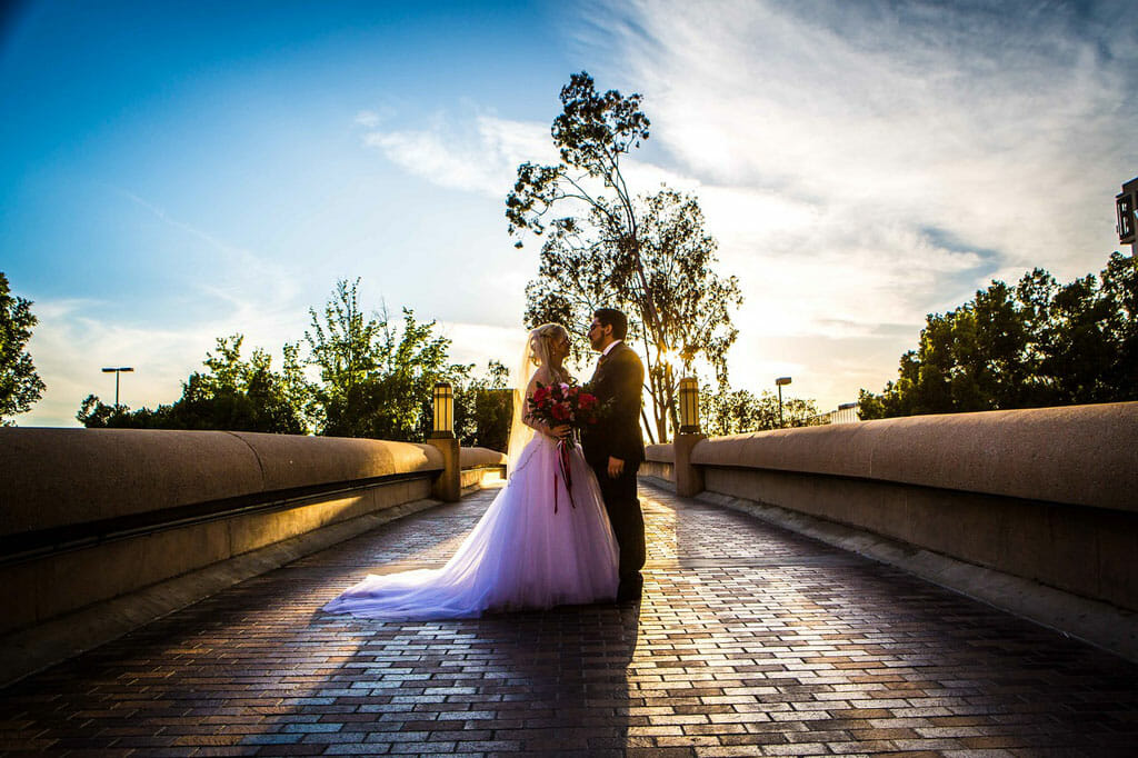 wedding couple embracing on noor's bridge to love with a blue sky and golden hour lighting