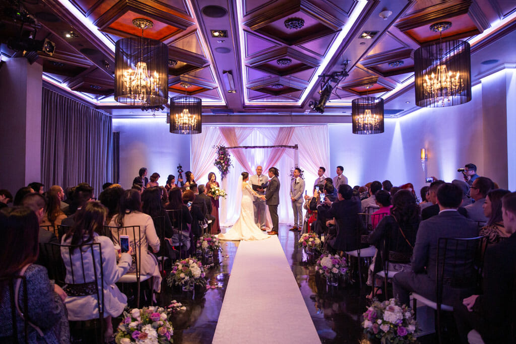 wedding ceremony couple exchanging vows under floral arch in noor's ella banquet hall