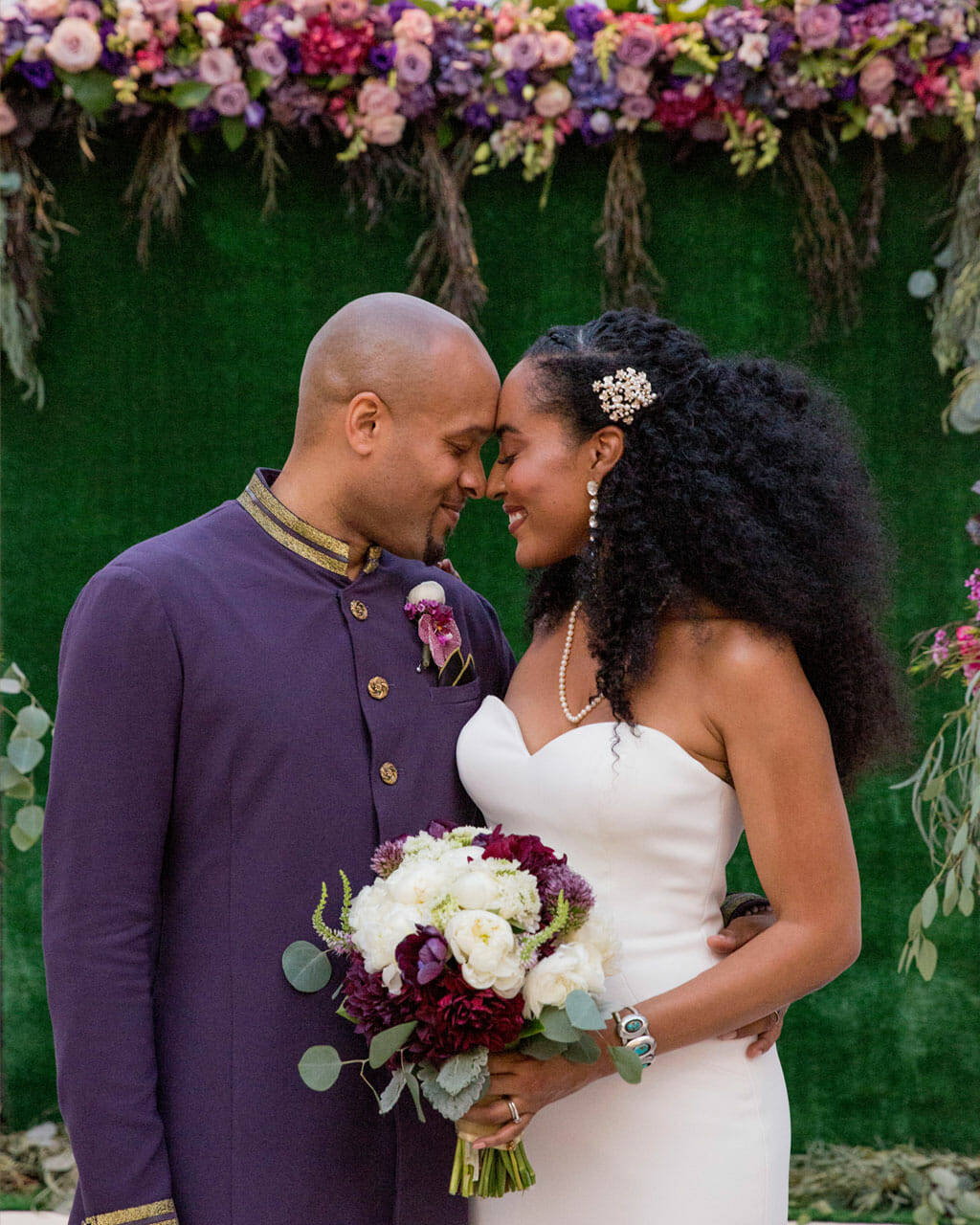 wedding couple smiling in front of ceremony flowers on the noor terrace los angeles