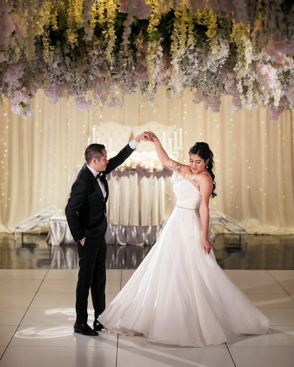 first dance under a canopy of flowers from a wedding at noor banquet hall in los angeles