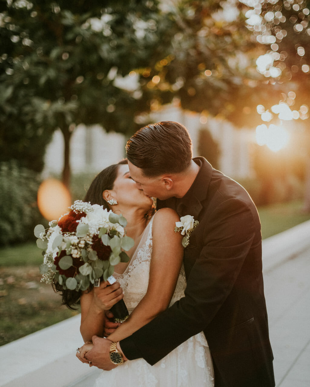 wedding couple with bouquet kissing in golden hour light near noor banquet halls pasadena