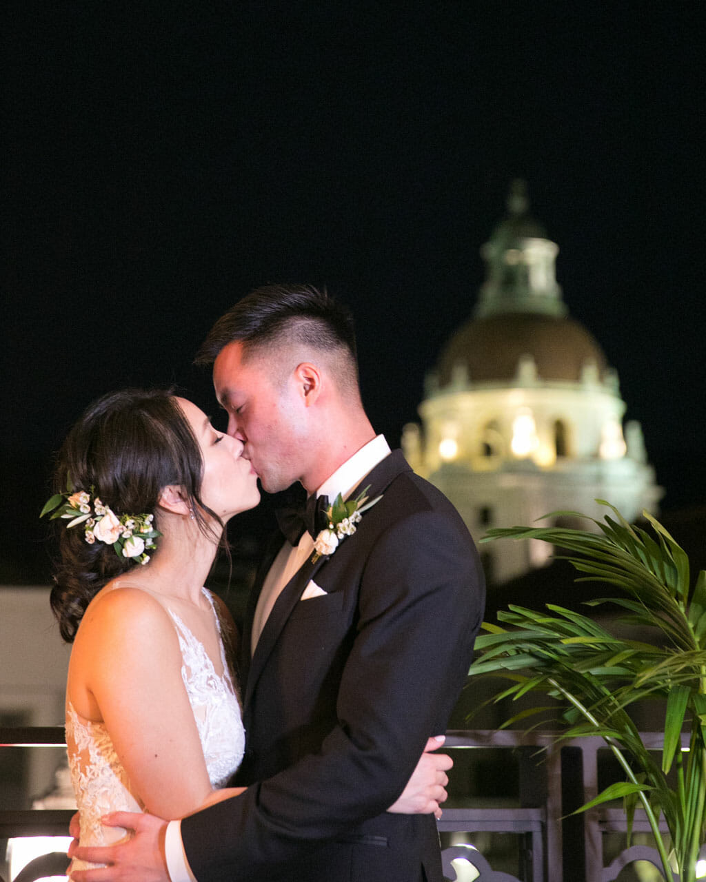 wedding couple kissing on noor's sofia banquet hall balcony with pasadena city hall behind