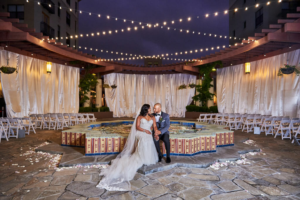 wedding couple sitting on the noor terrace fountain with draping and string lights in the background