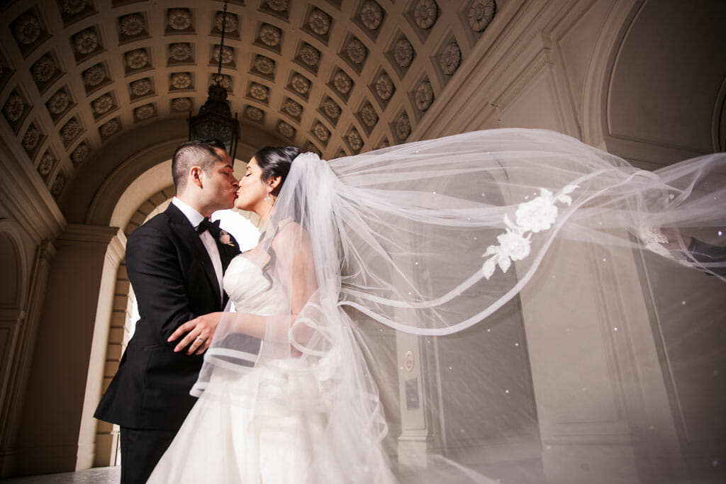 groom and bride kissing with flowing veil wedding portrait at pasadena city hall