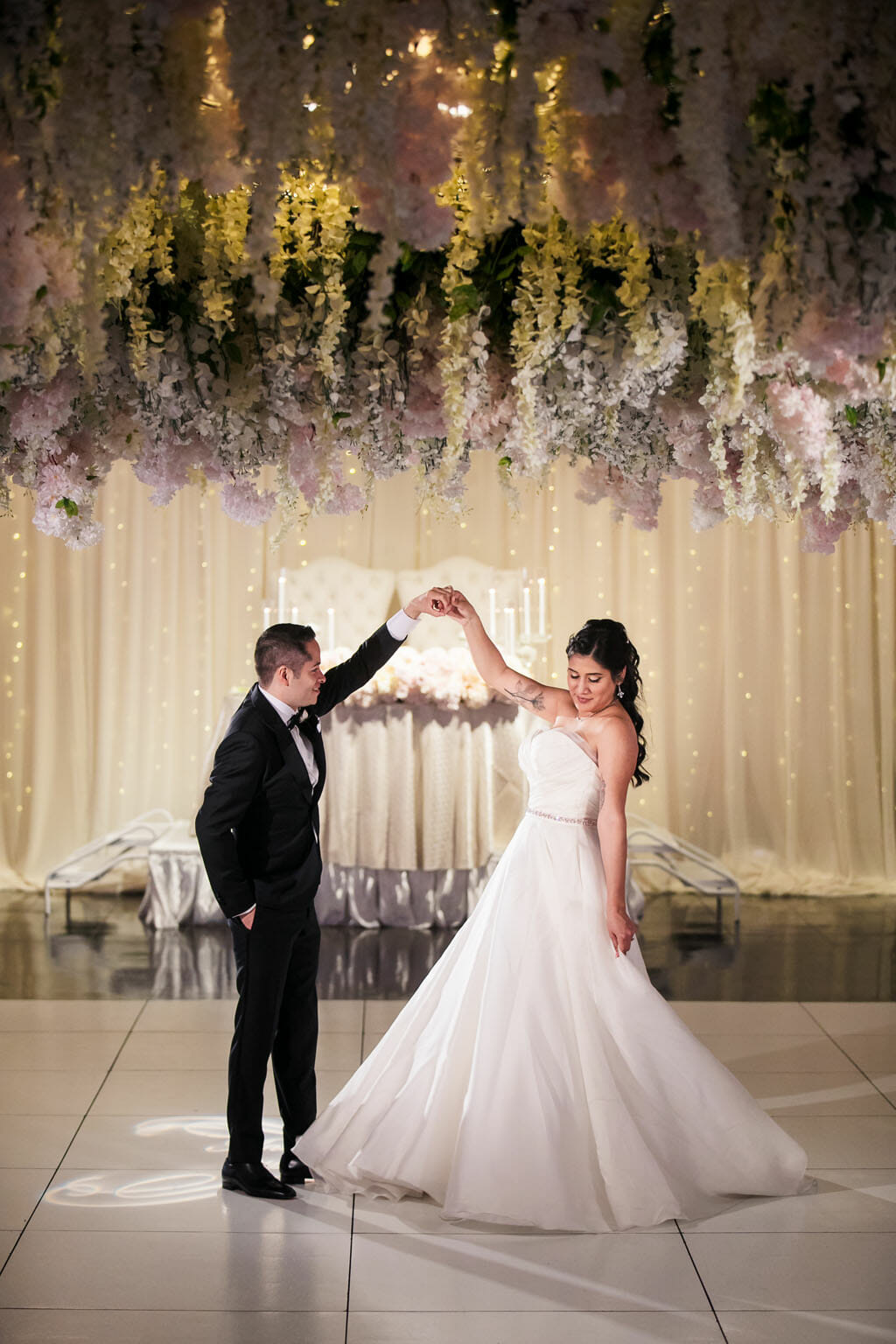 bride and groom dance under a wedding flower hanging ceiling