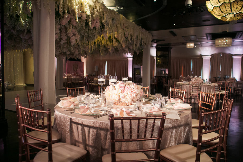 blush pink table decor wedding reception setup with floral hanging ceiling