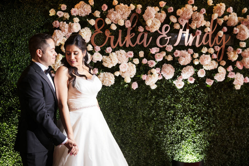bride and groom standing in front of flower wall with green grass backdrop and pink flowers and their names in gold