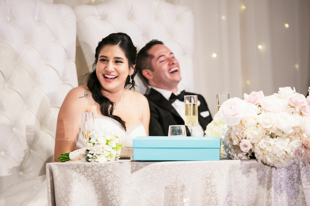 bride and groom sitting at sweetheart table laughing at speeches