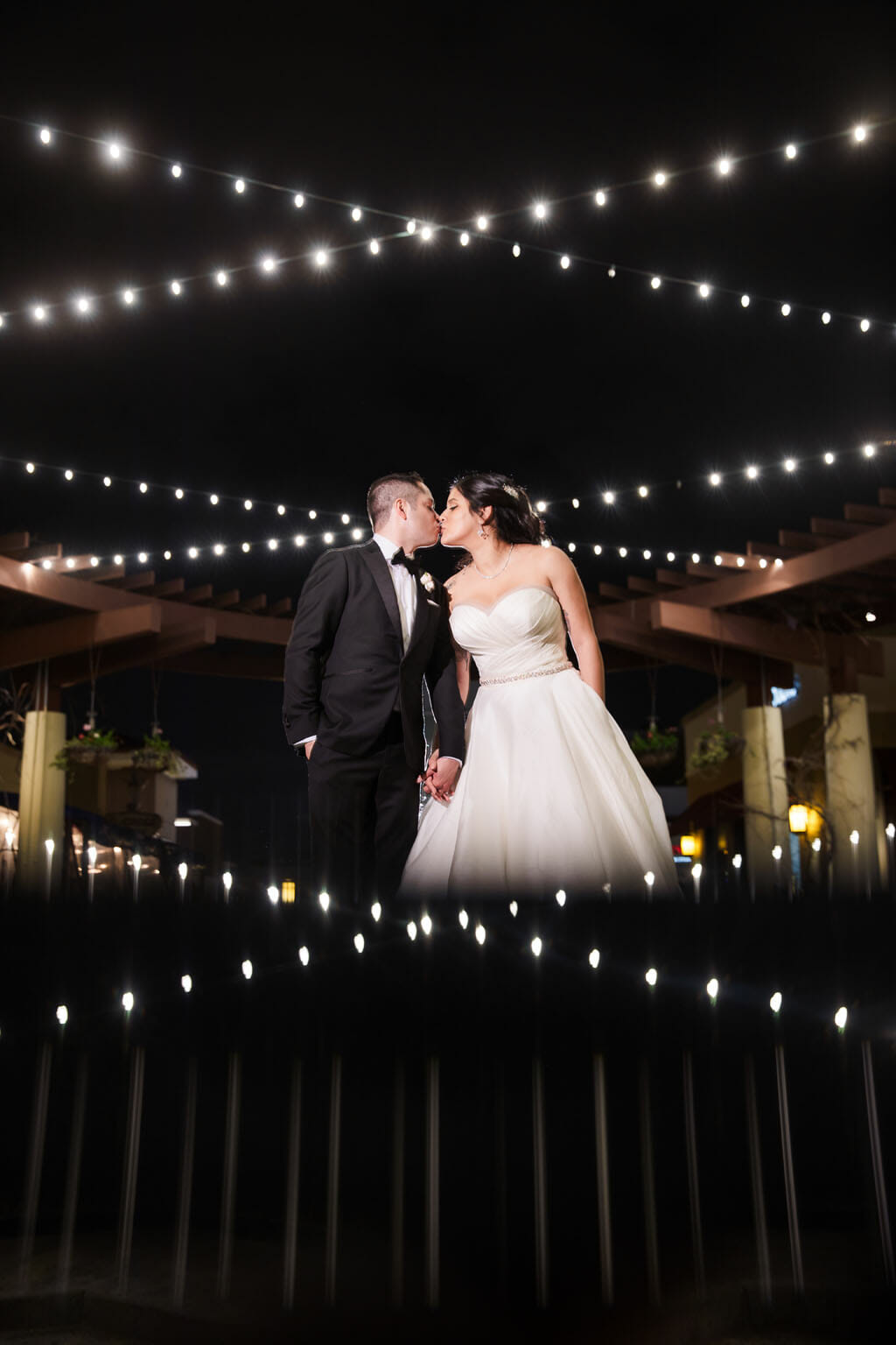 bride and groom kissing under string lights on the terrace at noor
