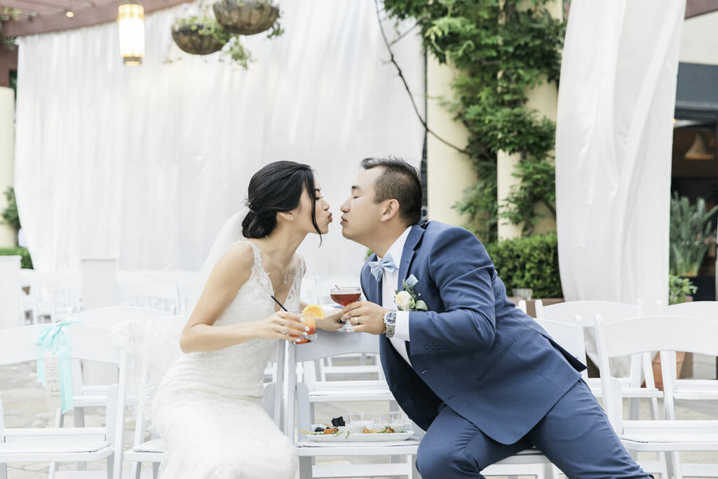 couple kissing and holding cocktails after outdoor wedding ceremony