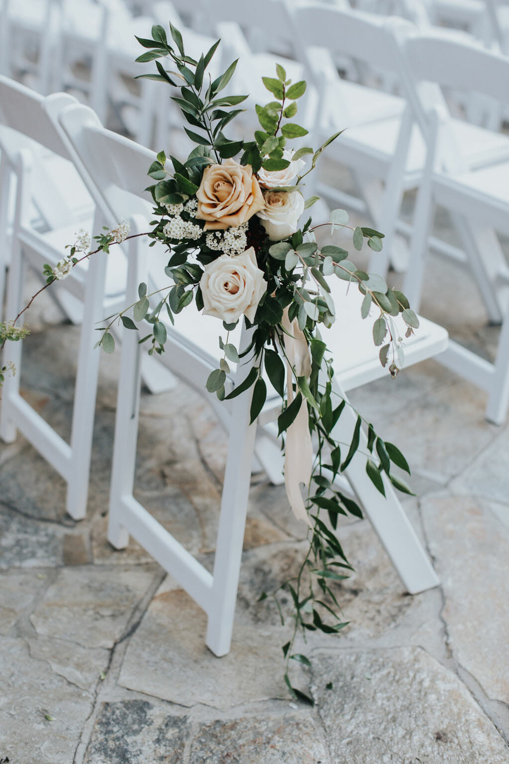 roses and greenery floral details at outdoor wedding ceremony