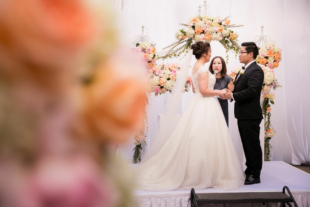 bride and groom saying vows in front of beautiful floral arch on the NOOR TERRACE